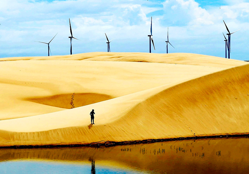 Wind turbines sit on a desert horizon.