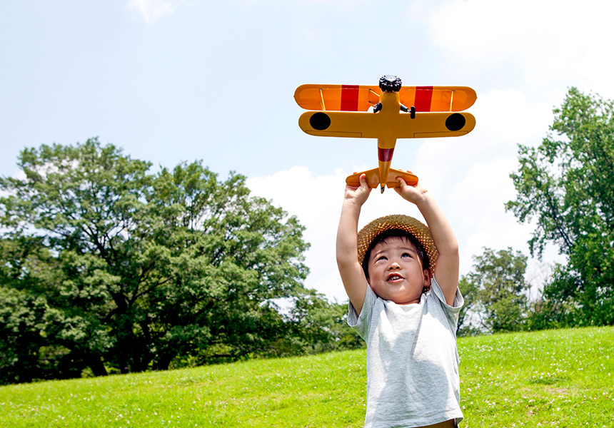 A little boy plays with a toy airplane in a field.