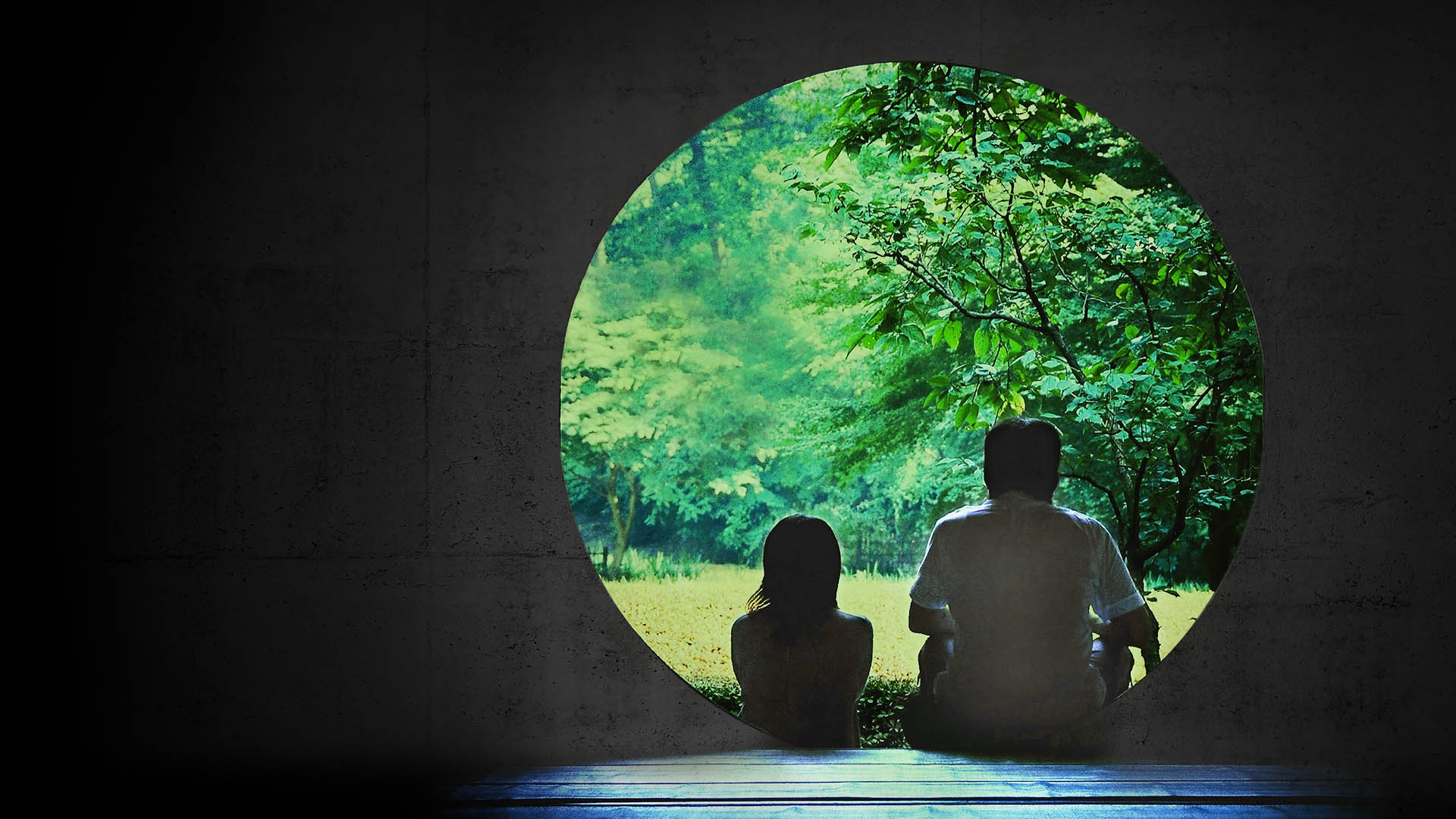 Two silhoetted people sit in front of a circular doorway, looking at green trees