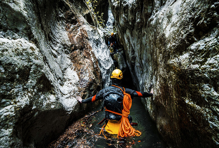 A canyoneering adventurist making his way through the wet gorge bottom