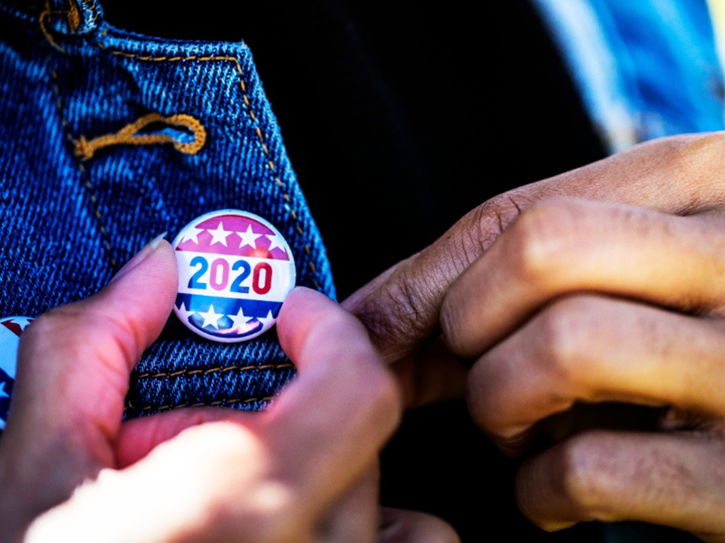 A voter places a 2020 election pin onto their jacket.