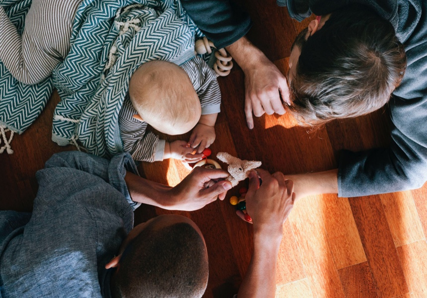 Overhead view of gay fathers playing with baby on a hardwood floor.