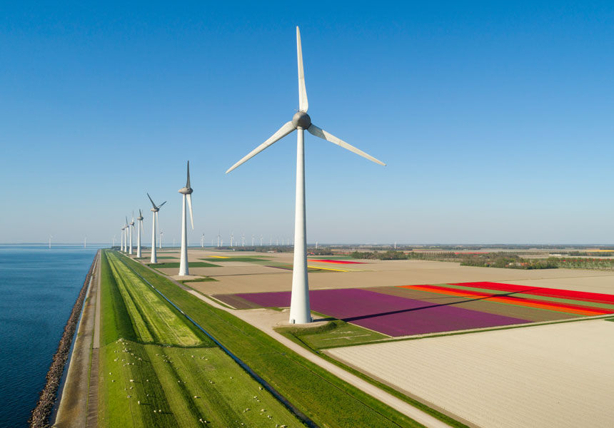 On and offshore wind turbines along a sunny flat coastline in the Netherlands